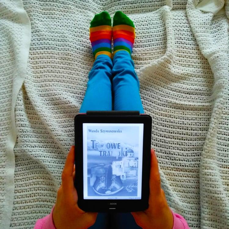 """Zdjęcie z czytnikiem, na którym znajduje się książka """"Tęczowe trampki"""""""